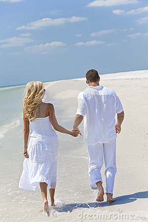 Happy Young Couple Walking Holding Hands on Beach