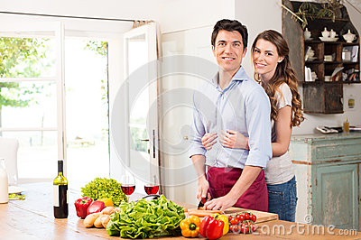 Happy Young Couple Working In Kitchen