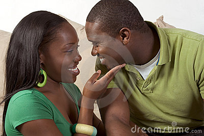 Happy young ethnic black couple sitting on couch