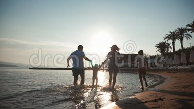 Happy young family have fun walking on beach at sunset. Family silhouette travel holiday. Happy young family have fun walking on beach at sunset. Family stock video