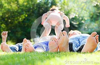 Happy young family lying on green grass outdoors