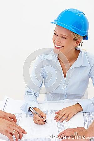 Happy young female architect marking blueprints