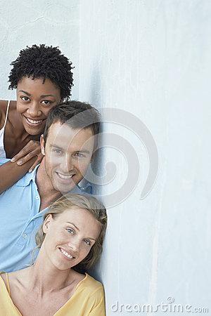 Happy Young Friends Leaning Against Wall