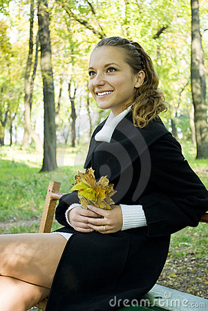 Happy young girl enjoying autumn in the park