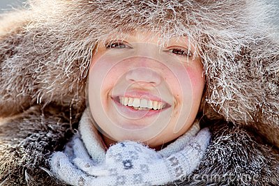Happy young girl in a fur hat