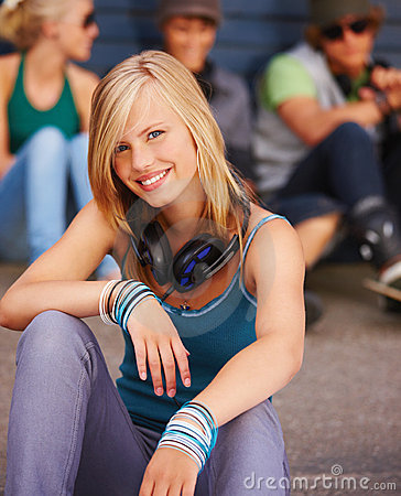 Happy young girl sitting with friends in the backg