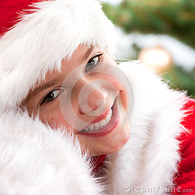 Happy young girl smiling  near the Christmas tree.