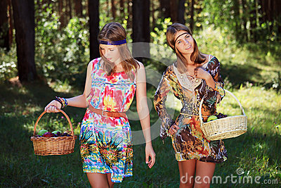 Happy young fashion girls walking in a forest