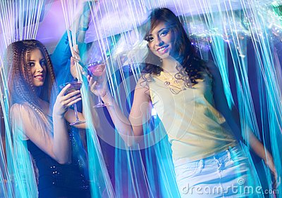 Happy young girls at night club