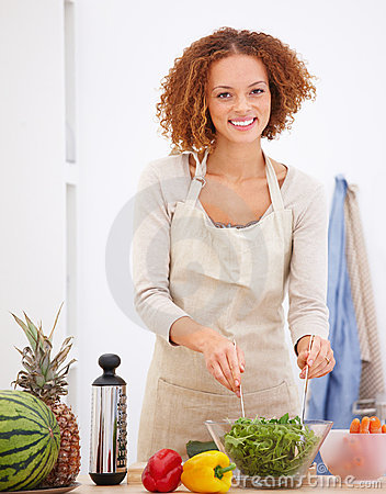 Happy young lady preparing food in a kitchen