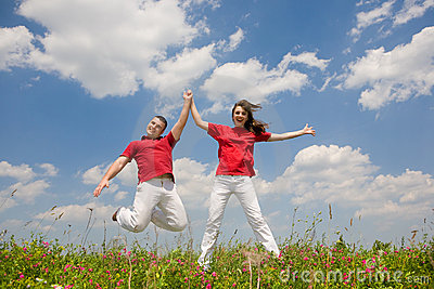 Happy Young love Couple - jumping under sky