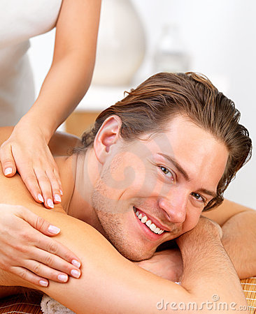 Happy young man getting back massage