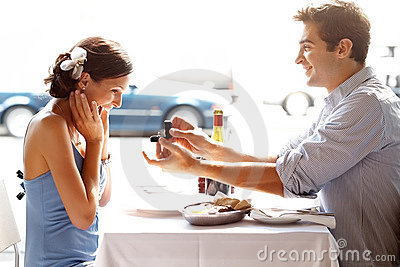 Happy young man gifting a ring to a woman