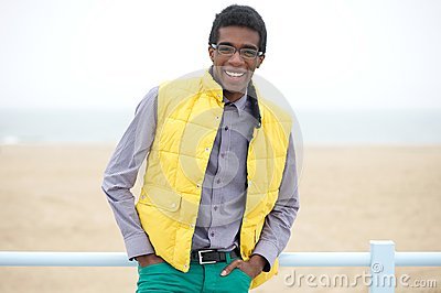 Happy young man with glasses and wearing colorful clothing