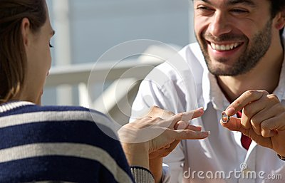 Happy young man proposing marriage to woman with engagement ring