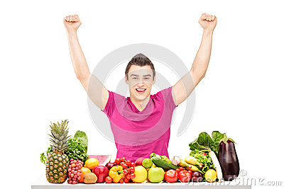 Happy young man raising hands and sitting behind a pile of fruit