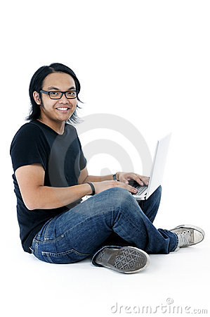 Happy young man sitting on floor with laptop