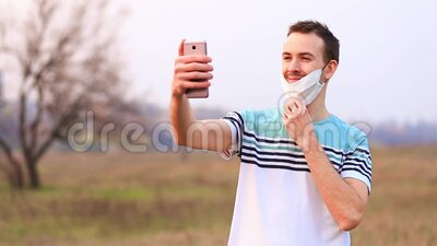 Happy young man in sterile face mask making video call with mobile phone show hello gesture walking outdoor. By street stock footage