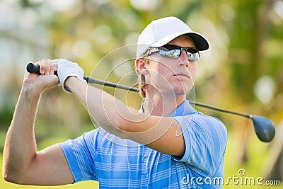 Happy young  man swinging golf club