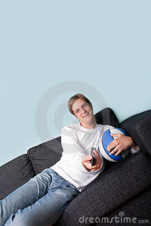 Happy young man watching sport on tv