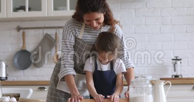 Happy young mommy helping little preschool daughter using rolling pin. Happy young mommy helping little preschool daughter using rolling pin, preparing dough stock footage