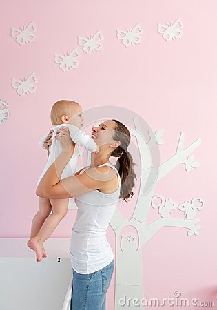 Happy young mother lifting baby from crib at home