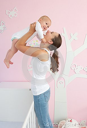 Happy young mother lifting cute baby out of crib