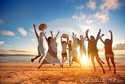 Happy young people jumping at the beach on beautiful sunset