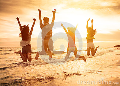 Happy young people jumping on the beach