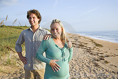 Happy young pregnant couple standing on beach