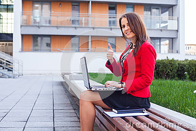 Happy young professional business woman sitting outdoor with com