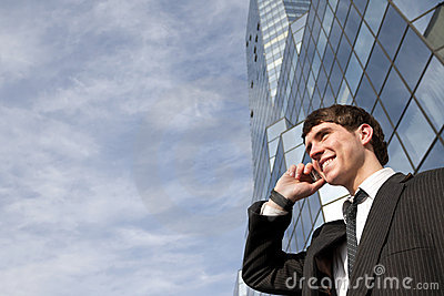 Happy young scuccessful businessman on phone