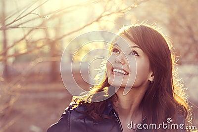 Happy young smile woman sunlight city portrait
