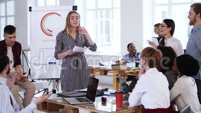 Happy young smiling blonde finance coach woman teaching multiethnic workers, leading team discussion at modern office. Intelligent positive experienced female stock video