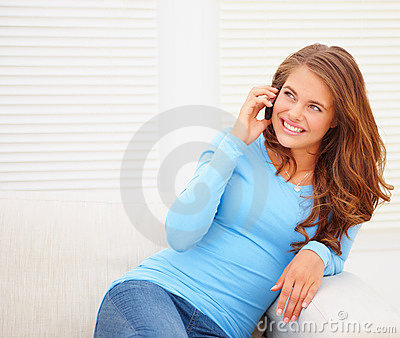 Happy young teenaged girl speaking over the phone