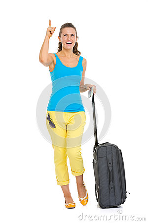 Happy young tourist woman with wheel bag pointing on copy space