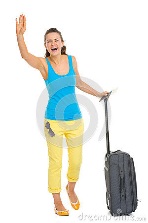 Happy young tourist woman with wheel bag saluting
