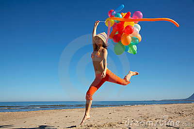 Happy young woman with balloons jumping
