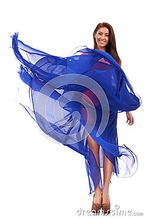 Happy young woman in blue long wavy dress