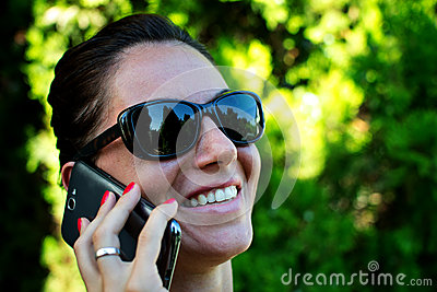 Happy young woman calling on mobile phone