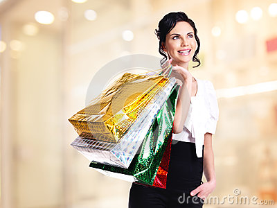 Happy young woman with color bags.