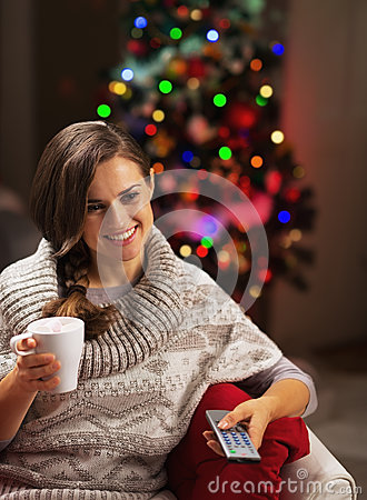 Happy young woman with cup of hot chocolate watching tv