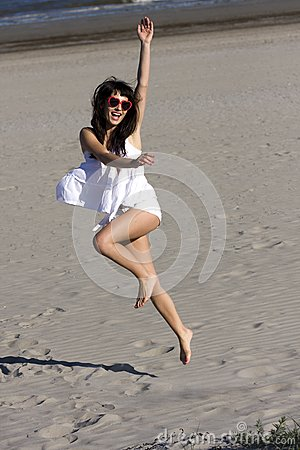 Happy young woman is dancing on the beach