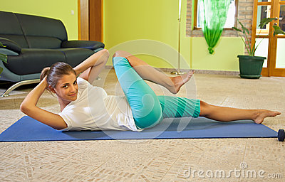 Happy young woman doing fitness at home.