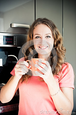 Happy young woman drinking coffee at home in the morni