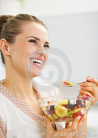 Happy young woman eating fresh fruits salad