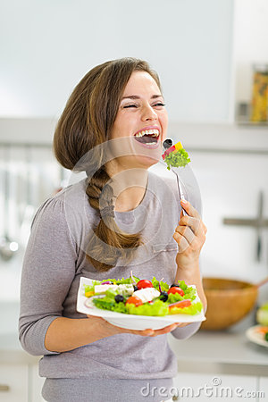 Happy young woman eating fresh salad
