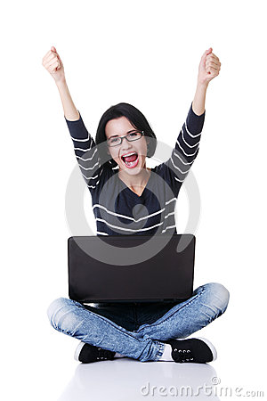 Happy young woman with fists up using her laptop