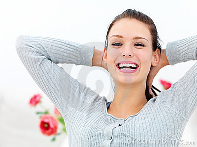Happy young woman with hands behind neck