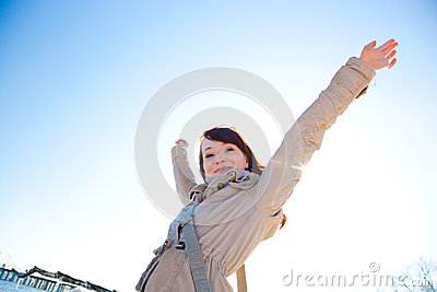 Happy young woman with hands up, sunny day.